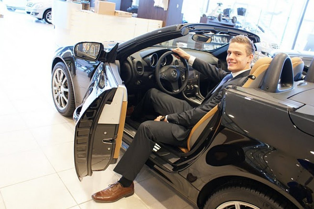 Student poseert in een mooie bolide in de Showroom van het Automotive College