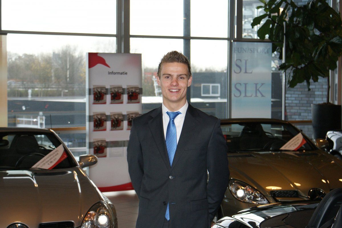 Student poseert in de showroom bij Automotive College
