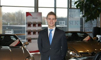 Student poseert  in de showroom van Automotive College